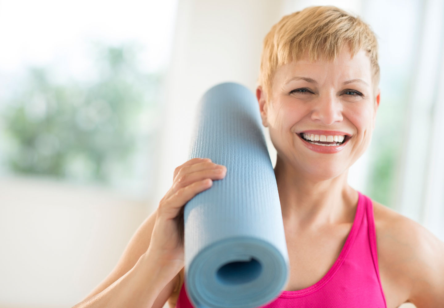 Confident woman with pilates mat